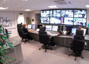 3 people monitoring Houston video surveillance footage on large screens